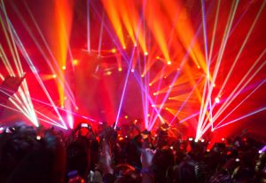 Rock concert background, large group of people enjoying party, having fun in night club in bright red laser light, active night life, music star performance